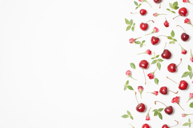 Composition of red blooms, cherries and green leaves Free Photo