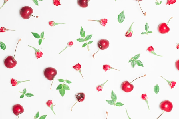Composition of red flowers, cherries and green leaves Free Photo