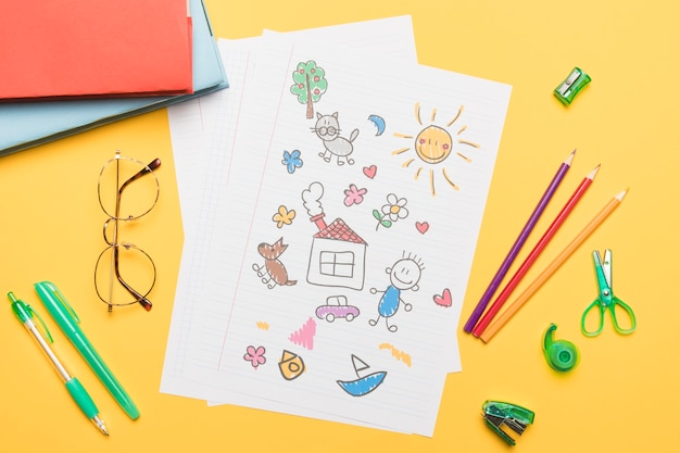 Composition of school stationery with drawing Free Photo