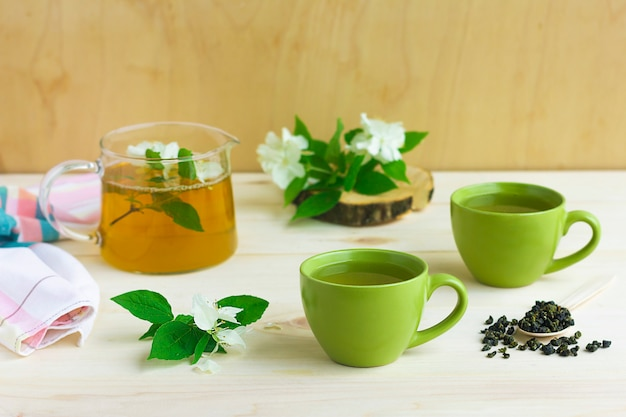 Композиция с двумя чашками зеленого травяного чая с цветком жасмина и чайником Premium Фотографии