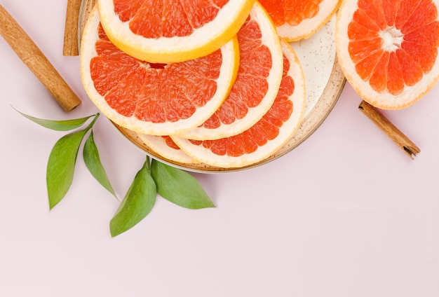 Free Photo | Composition of slices of grapefruit on dish and green leaves  near cinnamon