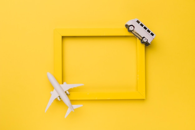 Composition of small white plane and bus on yellow frame Free Photo