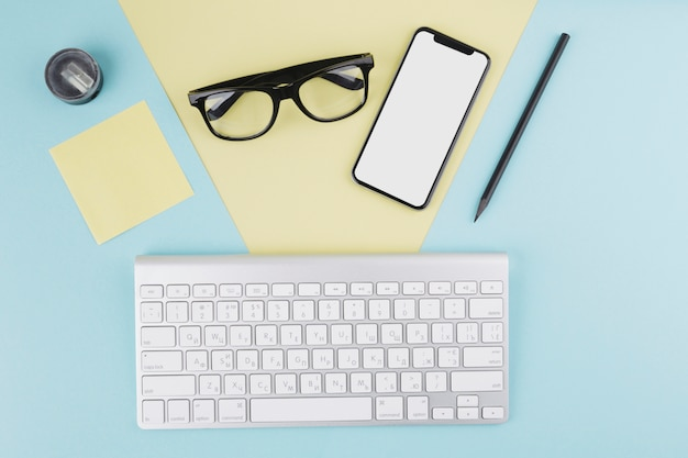 Composition of smartphone, keyboard, eyeglasses and pencil Free Photo