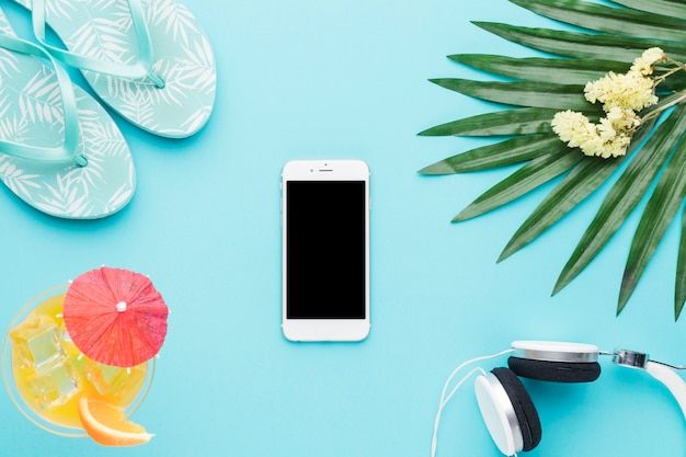 Composition of smartphone sandals beverage earphones green leaf and flowers Free Photo