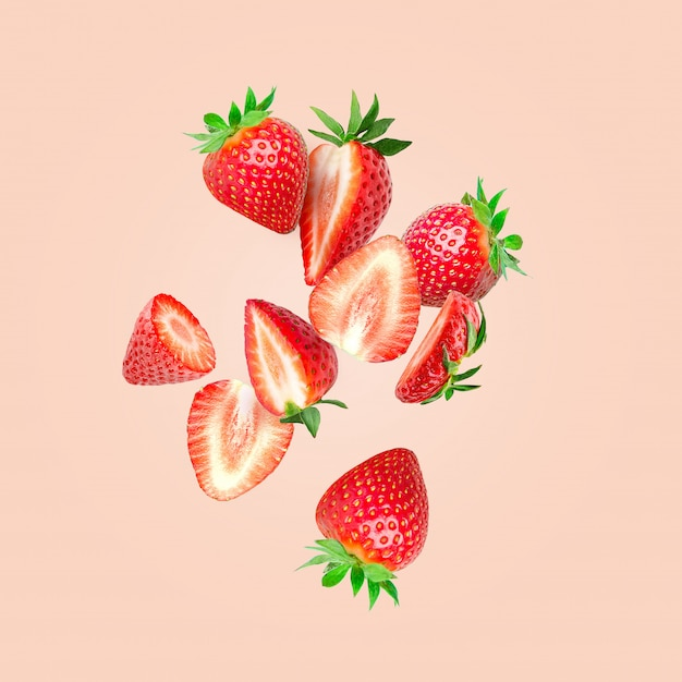 The composition of strawberries. cut strawberries into pieces flying in the air Premium Photo