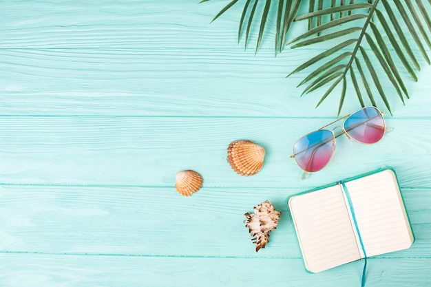 Composition of sunglasses with notebook and palm leaves Free Photo