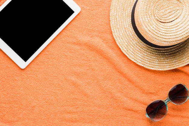 Composition of tablet sunglasses and hat Free Photo
