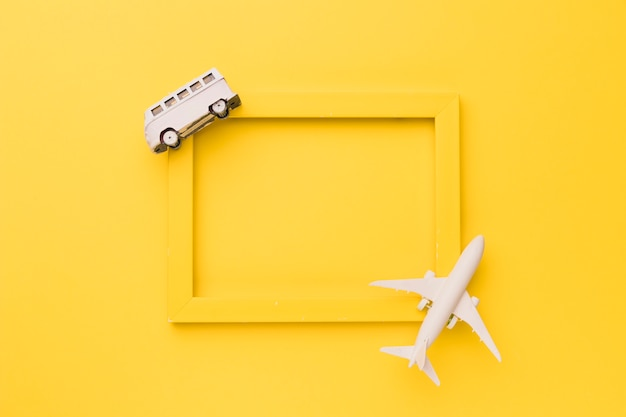 Composition of toy airplane and bus on yellow frame Free Photo