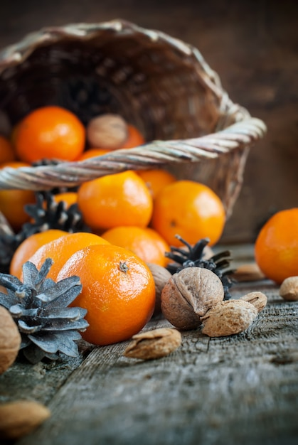 Composition with basket,tangerines and nuts wooden background Premium Photo