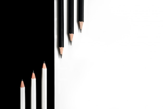 Composition with black pencils on a white background and white pencils on a black background Premium Photo