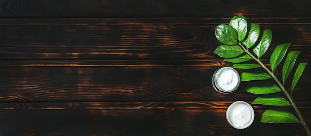 Composition with body care products, wisp and green leaf on old wooden table, top view Premium Photo