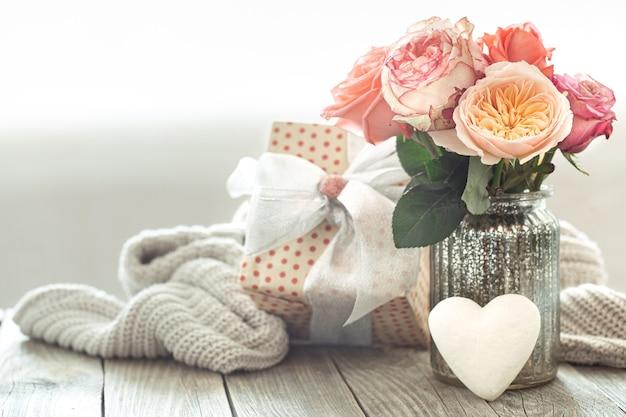 Composizione con bouquet di rose in vaso di vetro con confezione regalo Foto Gratuite