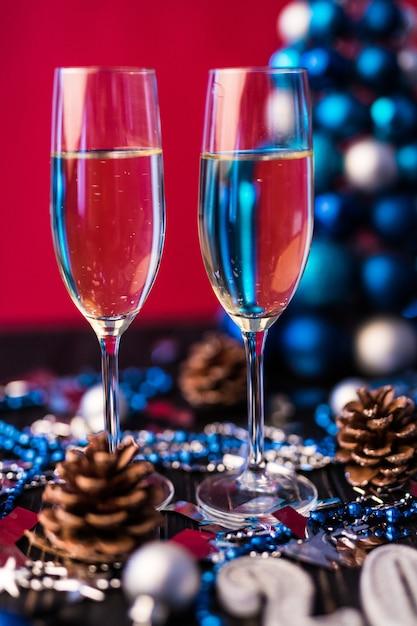 Композиция с рождественскими и новогодними украшениями 2020 и двумя бокалами для шампанского на ярком фоне Бесплатные Фотографии