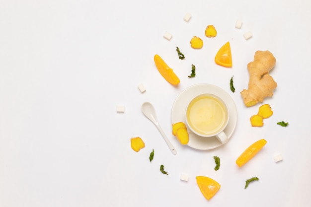 Composition with cup of tea, fresh orange, mint and sugar Premium Photo