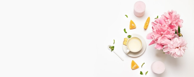 Composition with cup of tea, peone flowers, fresh orange, mint and sugar Premium Photo