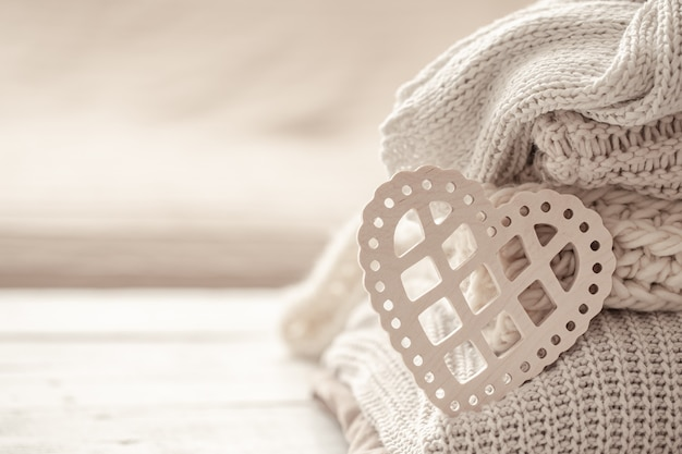 Composition with a decorative heart on the background of neatly folded warm clothes. Free Photo
