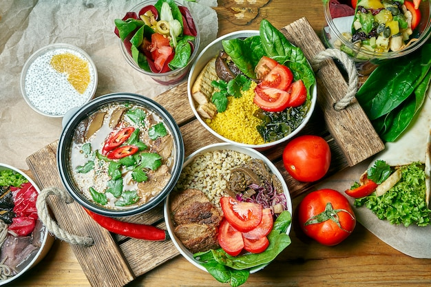 Composition with a dinner table with vegetarian dishes: bowl, dessert and miso soup on a gray cloth. healthy and balanced food. menu photo, top view Premium Photo