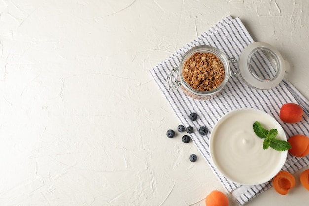 Composition with granola, yogurt and fresh fruits on white cement background Premium Photo