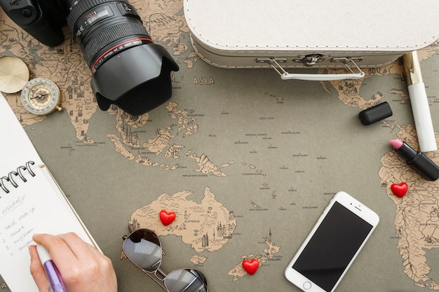 Composition with hand writing next to travel items Free Photo