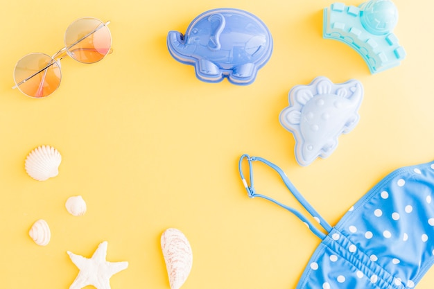 Composition with holiday summer beach accessories on yellow background Free Photo
