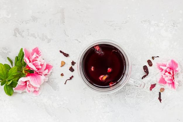 ピンクの花と乾燥茶葉のガラスのマグカップで熱いハイビスカスティーと組成。上面図。 Premium写真