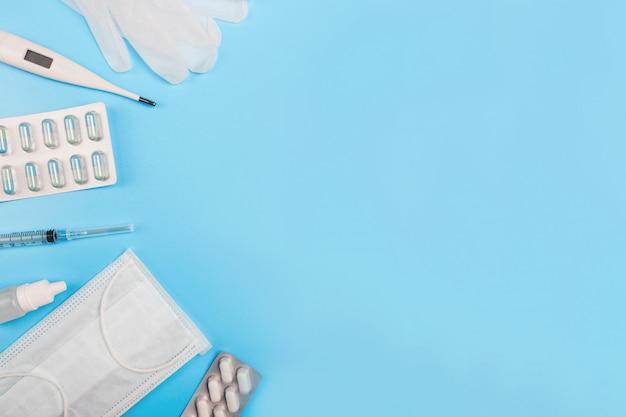 Композиция с медицинская маска, термометр, шприц, таблетки и перчатки на синем фоне. copyspace. Premium Фотографии