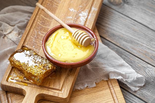 Composizione con miele naturale e mestolo di miele su fondo in legno si chiuda. Foto Gratuite