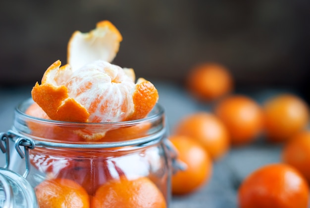 Composition with open tangerines in a jar Premium Photo