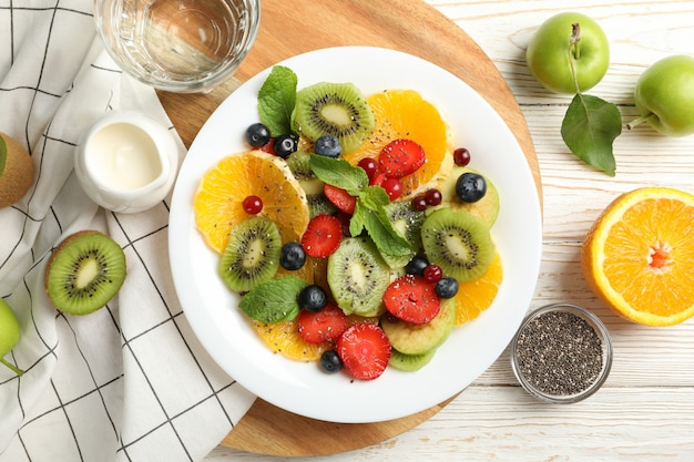 Composition with plate of fresh fruit salad on white wooden table, top view Premium Photo