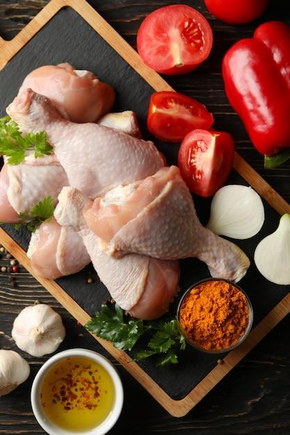 Композиция с сырым куриным мясом на деревянном пространстве, вид сверху Premium Фотографии