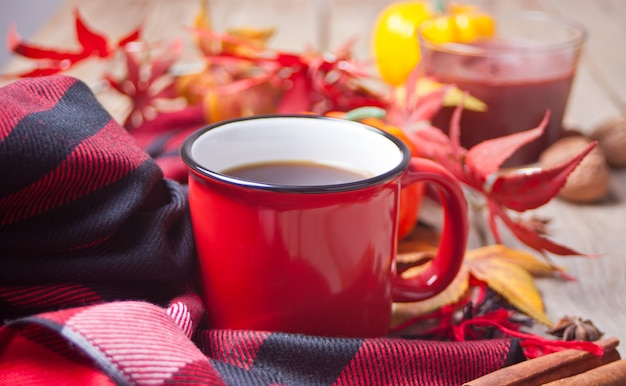 コーヒー、紅葉、小さなカボチャと赤いマグカップのコンポジション Premium写真