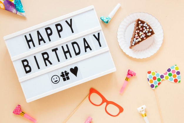 Composition with sliced cake and birthday lettering Free Photo
