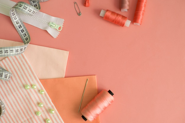 Composition with threads and sewing accessories on color background, flat lay Premium Photo