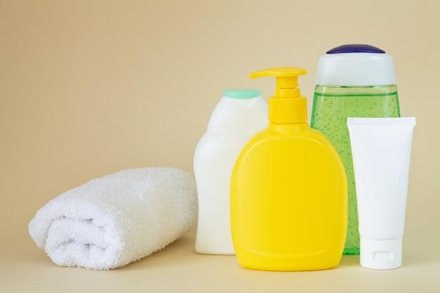 Композиция с полотенцем и пластиковыми бутылками для ухода за телом с копией пространства Premium Фотографии