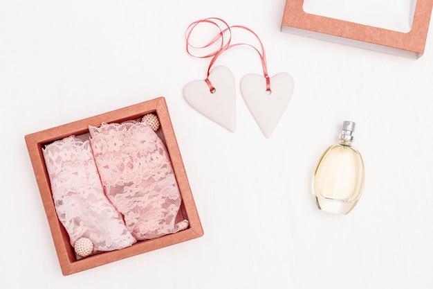 Композиция с белыми сердечками вместе с розовой ленточкой, кружевным женским бельем и парфюмом Premium Фотографии