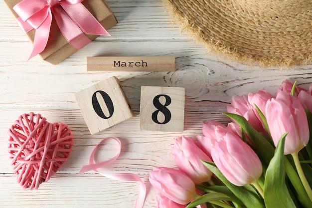 木製のカレンダーと木製の背景、上面にチューリップの組成 Premium写真