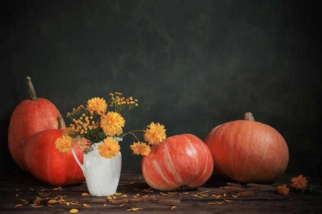 Композиция с желтыми цветами и тыквы на старый деревянный стол Premium Фотографии