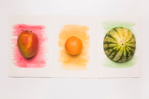 Composition of yummy whole mixed fruits on multicolored watercolor surface Free Photo