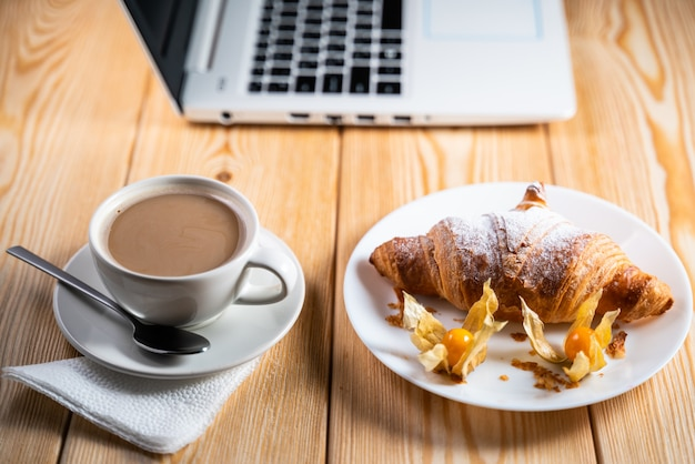 Computer, cup coffee and croissant on brown wood table Premium Photo