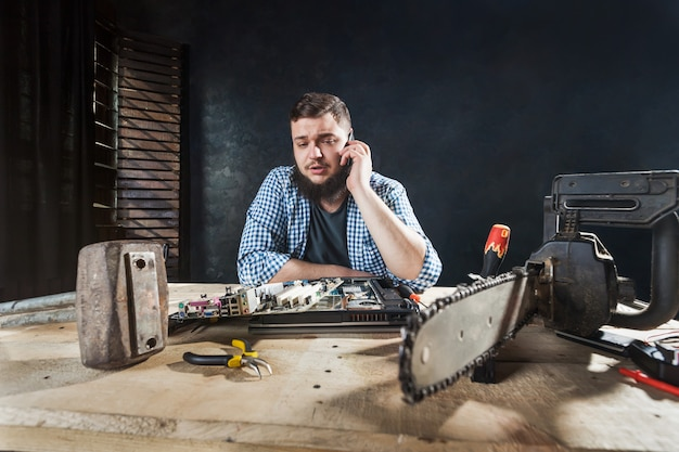 Computer engineer talk with client by phone about problem with electronic components of laptop. chainsaw and anvil on the table, engineering humor Premium Photo