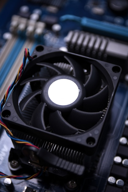 Computer fan on motherboard and electronical components cpu gpu memory and different sockets for video card close up Premium Photo