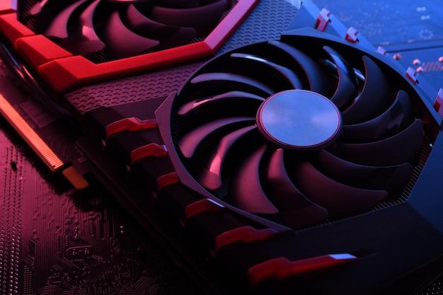 コンピュータゲームのグラフィックカード、回路基板上の2つのクーラーを備えたビデオカード、マザーボードのテーブル。閉じる。赤青の照明付き。 Premium写真