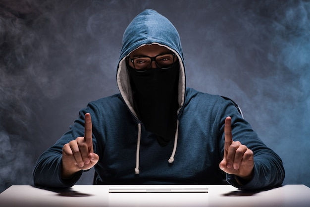 Computer hacker working in dark room Premium Photo