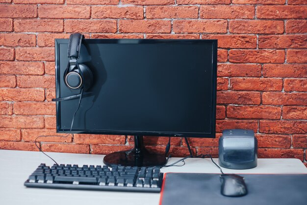 Computer headphones keyboard mouse on table on brick background at home Premium Photo