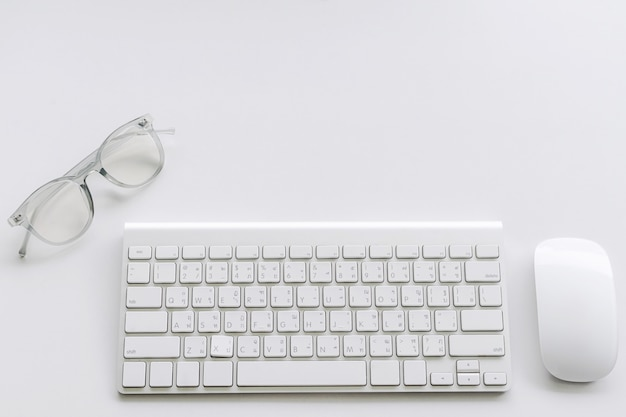 Computer keyboard and mouse with glasses on white background Premium Photo
