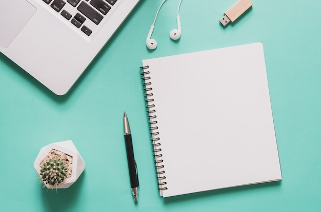 Computer laptop with blank notebook, cactus, pen, flash drive, earphone on blue background. Premium Photo