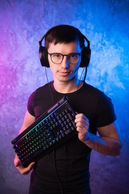 Computer nerd with keyboard over colorful pink and blue neon lit wall Premium Photo