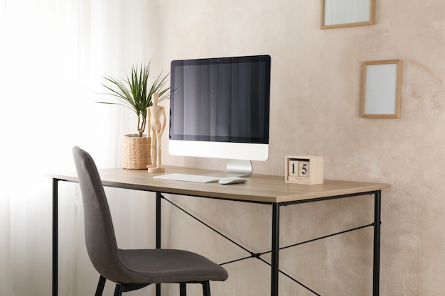 Computer, plant and wood man on wooden table. workplace room Premium Photo