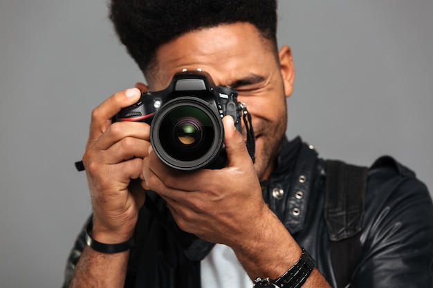 Concentrated afro american man taking photo on digital camera Free Photo