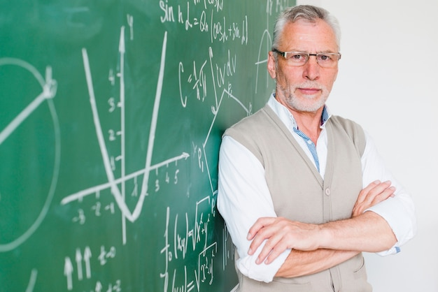 Concentrated aged math teacher leaning on chalkboard Free Photo